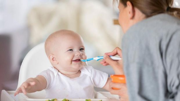 An adorable baby in a high chair laughs at her mother as she spoon feeds her.  She pretends the spoon is a moving train using sound effects.