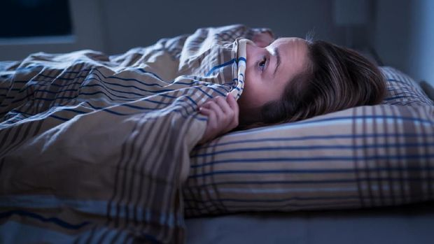 Scared woman hiding under blanket. Afraid of the dark. Unable to sleep after nightmare or bad dream. Awake in the middle of the night in bedroom at home.  Monster under the bed or in closet.