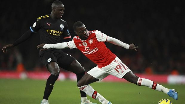Manchester City's Benjamin Mendy, left, fights for the ball with Arsenal's Nicolas Pepe during the English Premier League soccer match between Arsenal and Manchester City, at the Emirates Stadium in London, Sunday, Dec. 15, 2019. (AP Photo/Ian Walton)