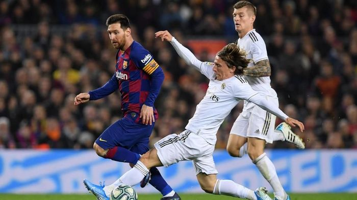 BARCELONA, SPAIN - DECEMBER 18:  Lionel Messi of Barcelona is tackled by Luka Modric of Real Madrid during the Liga match between FC Barcelona and Real Madrid CF at Camp Nou on December 18, 2019 in Barcelona, Spain. (Photo by Alex Caparros/Getty Images)