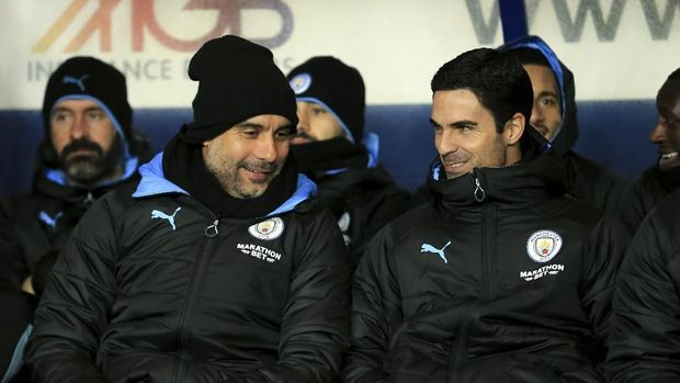 Manchester City's head coach Pep Guardiola and Mikel Arteta converse before the EFL Carabao Cup quarter finals soccer match between Oxford United and Manchester City at the Kassam Stadium, England, in Oxford, England, Wednesday, Dec. 18, 2019. (AP Photo/Leila Coker)