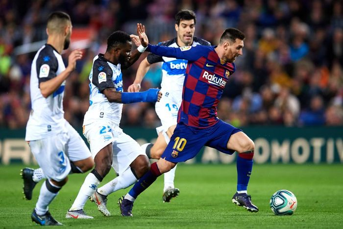 BARCELONA, SPAIN - DECEMBER 21: Lionel Messi of FC Barcelona eludes the pressure from Ruben Duarte, Wakaso Mubarak and Manu Garcia of Deportivo Alaves to score his teams third goal during the La Liga match between FC Barcelona and Deportivo Alaves at Camp Nou on December 21, 2019 in Barcelona, Spain. (Photo by Alex Caparros/Getty Images)