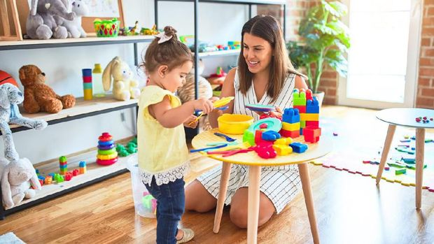 Young beautiful teacher and toddler playing with dishes and cutlery toy at kindergarten