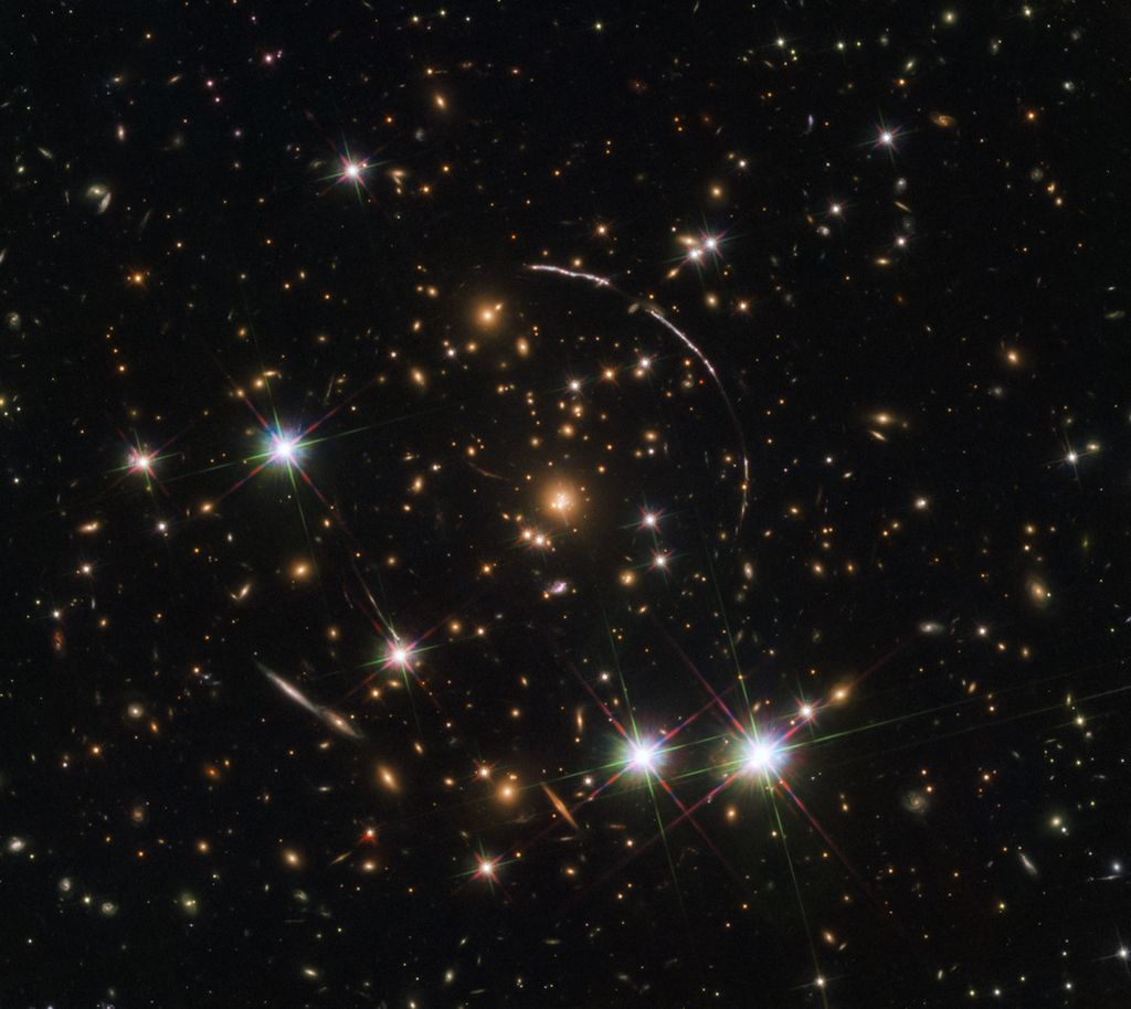 PSZ1 G311.65-18.48. Gugusan latar depan ini secara gravitasi memantulkan sebuah galaksi ultra-jauh ke yang luar biasa. Foto: NASA, ESA, E. Rivera-Thorsen (Institute of Theoretical Astrophysics, Oslo, Norway).