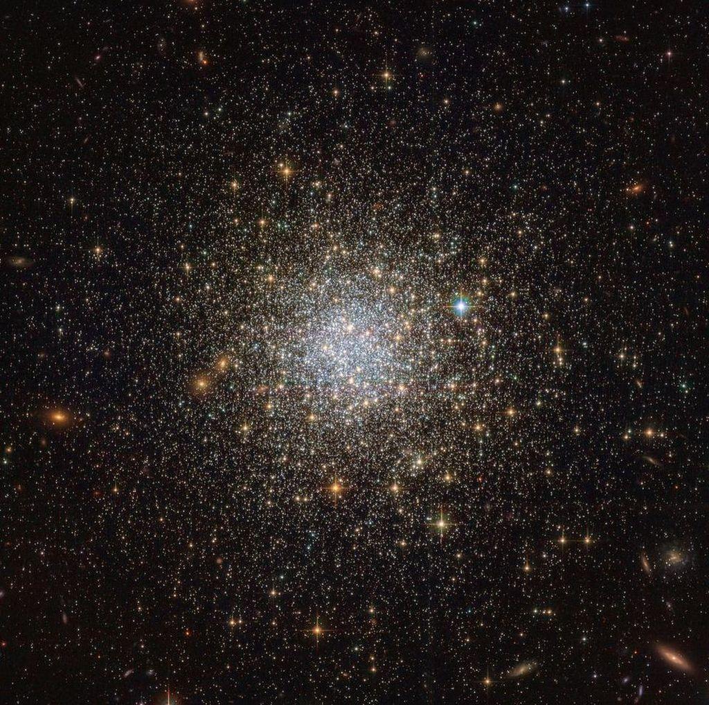 Gugus Globular NGC 1466. Gugusan bintang purba ini mengorbit Awan Magellan Besar, yang secara terpusat kaya akan kumpulan bintang kebiruan yang baru terbentuk. Foto: ESA, NASA.