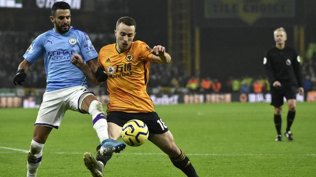 Wolverhampton Wanderers' Diogo Jota, right, challenges for the ball with Manchester City's Riyad Mahrez during the English Premier League soccer match between Wolverhampton Wanderers and Manchester City at the Molineux Stadium in Wolverhampton, England, Friday, Dec. 27, 2019. (AP Photo/Rui Vieira)
