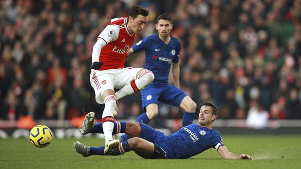 Arsenal's Mesut Ozil, left, is tackled by Chelsea's Cesar Azpilicueta during the English Premier League soccer match between Arsenal and Chelsea, at the Emirates Stadium in London, Sunday, Dec. 29, 2019. (AP Photo/Ian Walton)