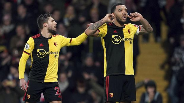 Watford's Troy Deeney, right, celebrates with Kiko Femenia after scoring against Aston Villa during the English Premier League soccer match at Vicarage Road, Watford, England, Saturday Dec. 28, 2019. (Tess Derry/PA via AP)