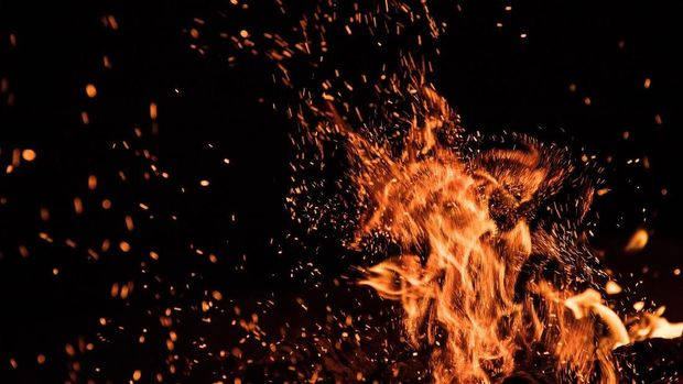 Burning sparks flying. Beautiful flames. Fiery orange glowing flying away particles on black background.