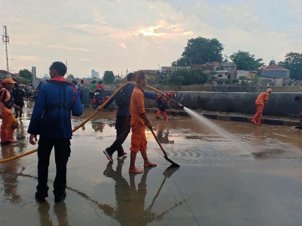 Banjir Surut, Damkar Jaktim Mulai Bersihkan Jalan Jatinegara Barat dari Lumpur
