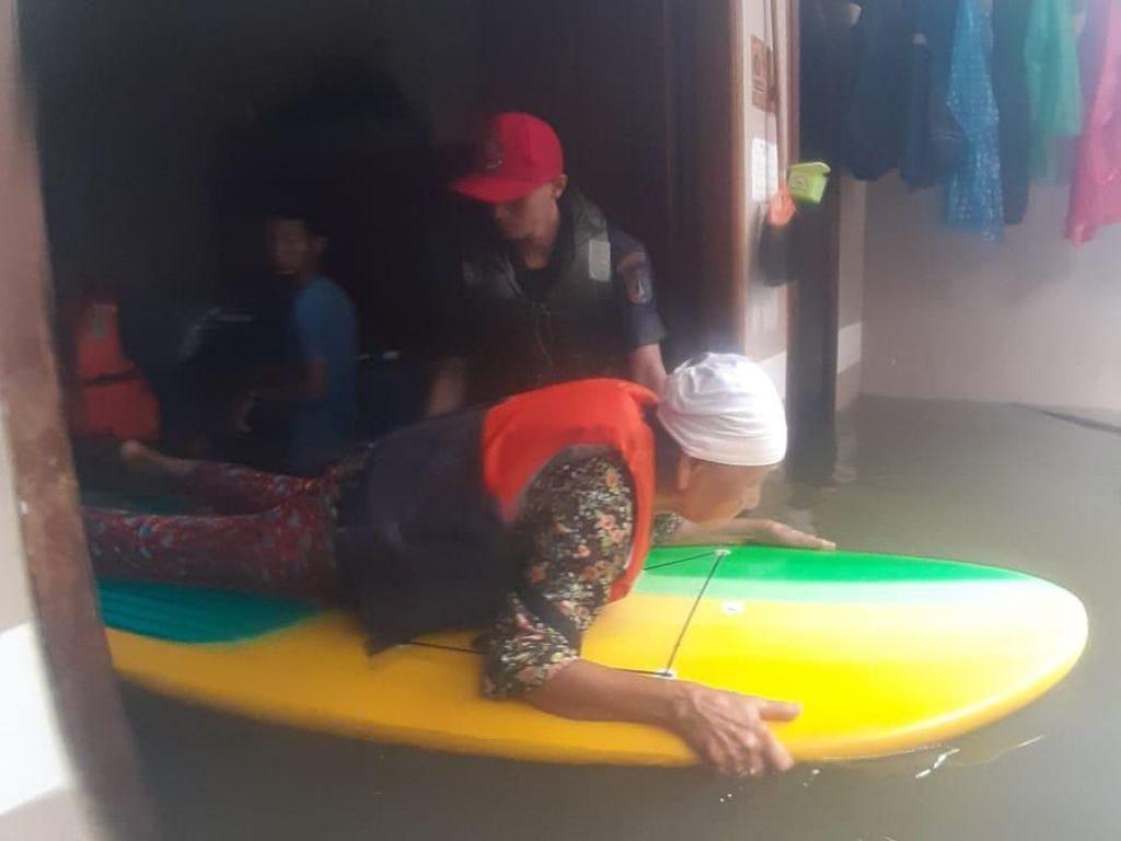 Pakai Papan Seluncur, Tim Damkar Evakuasi Korban Banjir di Cengkareng
