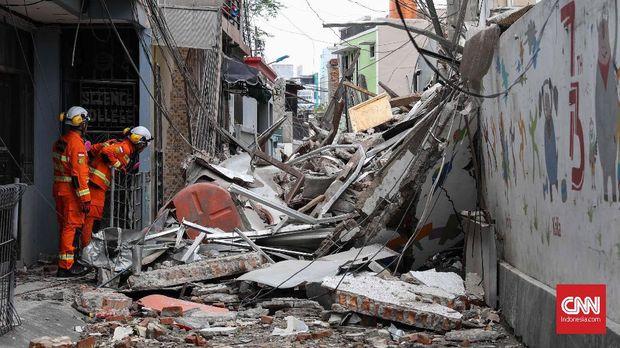 Reruntuhan ruko menimpa jalan kecil dan bagian depan rumah di sampingnya.