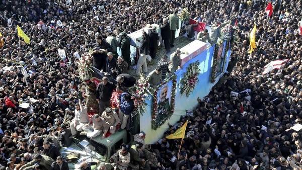 Foto: Peti yang berisi jenazah Qasem Soleimani dibawa dengan truk yang dikerumuni para pelayat di Kerman (AP Photo)