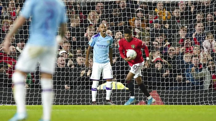 Manchester Uniteds Marcus Rashford, right collects the ball after scoring is sides first goal during the English League Cup semifinal first leg soccer match between Manchester United and Manchester City and at Old Trafford, Manchester, England, Tuesday, Jan. 7, 2020. (AP Photo/Jon Super)