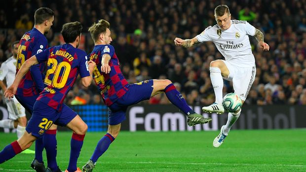 Barcelona's Croatian midfielder Ivan Rakitic (C) challenges Real Madrid's German midfielder Toni Kroos (R) during the