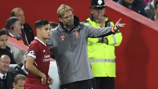 Liverpool's German manager Jurgen Klopp (C) speaks to Liverpool's Brazilian midfielder Philippe Coutinho as he prepares to play during the UEFA Champions League Group E football match between Liverpool and Sevilla at Anfield in Liverpool, north-west England on September 13, 2017. (Photo by Paul ELLIS / AFP)
