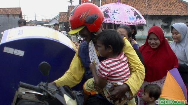 Tarmuji saat bekerja sambil menggendong anaknya