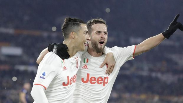 Juventus' Cristiano Ronaldo, left, celebrates with teammate Miralem Pjanic after scoring his side's second goal during the Serie A soccer match between Roma and Juventus at the Rome Olympic Stadium, Italy, Sunday, Jan. 12, 2020. (AP Photo/Andrew Medichini)