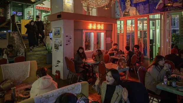 A photo taken on January 10, 2020 shows diners at the North Korean-themed Pyeongyang Bar in the Hongdae district of Seoul. - The Pyeongyang Bar is Seoul's only North Korean-themed bar and aims to give its South Korean patrons a taste of North Korean nightlife. Adorned with spoof propaganda slogans and imagery characteristic of the North, patrons can order typical North Korean dishes washed down with beverages bearing false North Korean brand labels -- which for now, due to trade and tourism blackout between the two countries, is the closest that most customers can expect to get to the real thing. (Photo by Ed JONES / AFP)