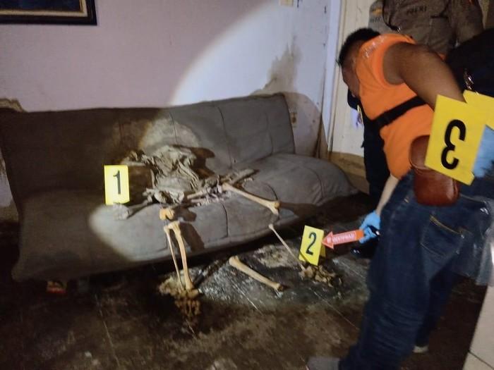 Polisi memeriksa kerangka manusia berposisi duduk di rumah kosong. (Foto: dok. Istimewa)
