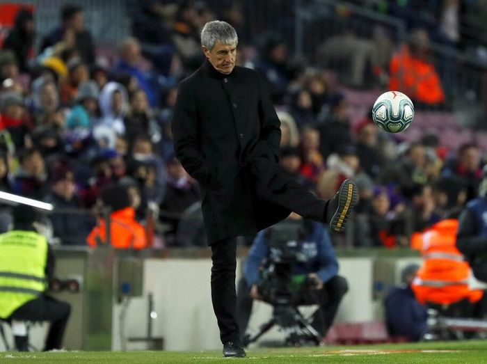 Barcelonas head coach Quique Setien kicks the ball back to the pitch during a Spanish La Liga soccer match between Barcelona and Granada at Camp Nou stadium in Barcelona, Spain, Sunday, Jan. 19, 2020. (AP Photo/Joan Monfort)