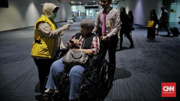 Petugas memantau suhu tubuh penumpang di bandara Soetta untuk mendeteksi suspect Virus Corona.