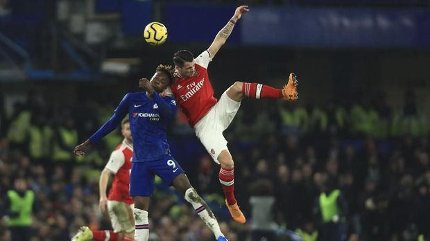 Chelsea's Tammy Abraham, left, challenges for the ball with Arsenal's Gabriel Martinelli during the English Premier League soccer match between Chelsea and Arsenal at Stamford Bridge stadium in London England, Tuesday, Jan. 21, 2020. (AP Photo/Leila Coker)