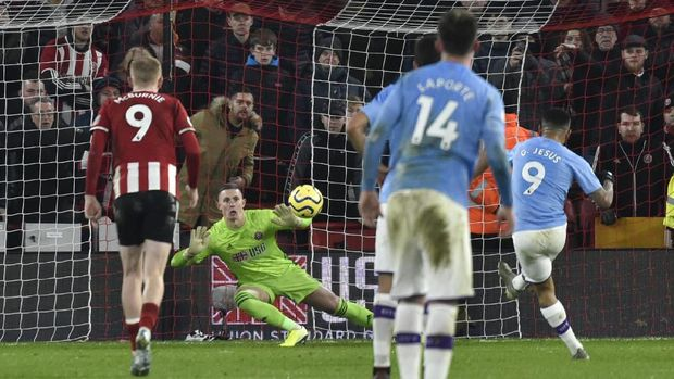 Sheffield United's goalkeeper Dean Henderson keep a save the penalty from Manchester City's Gabriel Jesus, right, during the English Premier League soccer match between Sheffield United and Manchester City at Bramall Lane in Sheffield, England, Tuesday, Jan. 21, 2020. (AP Photo/Rui Vieira)