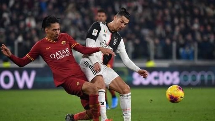 AS Romas English defender Chris Smalling (L) and Juventus Portuguese forward Cristiano Ronaldo go for the ball during the Italian Cup (Coppa Italia) round of 8 football match Juventus vs AS Roma on January 22, 2020 at the Juventus stadium in Turin. (Photo by Marco Bertorello / AFP)