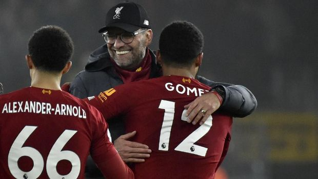 Liverpool's manager Jurgen Klopp, center, celebrates with Liverpool's Trent Alexander-Arnold, left, and Liverpool's Joe Gomez at the end of the English Premier League soccer match between Wolverhampton Wanderers and Liverpool at the Molineux Stadium in Wolverhampton, England, Thursday, Jan. 23, 2020. (AP Photo/Rui Vieira)
