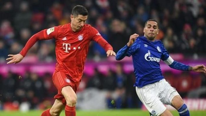 Bayern Munichs Polish striker Robert Lewandowski (L) and Schalkes Spanish midfielder Omar Mascarell (R) vie for the ball during the German first division Bundesliga football match Bayern Munich v Schalke 04 in Munich on January 25, 2020. (Photo by Christof STACHE / AFP) / DFL REGULATIONS PROHIBIT ANY USE OF PHOTOGRAPHS AS IMAGE SEQUENCES AND/OR QUASI-VIDEO
