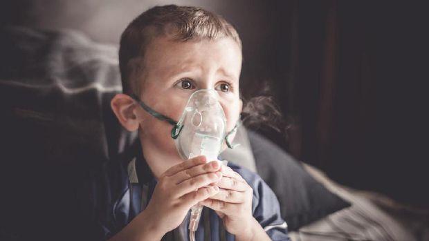 Two year old boy making inhalation with nebulizer at home. child asthma inhaler inhalation nebulizer steam sick cough concept Horizontal