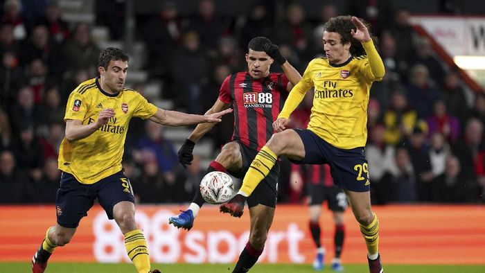 Bournemouths Dominic Solanke, center, battles for the ball Arsenals Sokratis Papastathopoulos, left, and Matteo Guendouzi during the English FA Cup fourth round soccer match between AFC Bournemouth and Arsenal at Vitality Stadium, Bournemouth, England, Monday, Jan. 27, 2020. (John Walton/PA via AP)