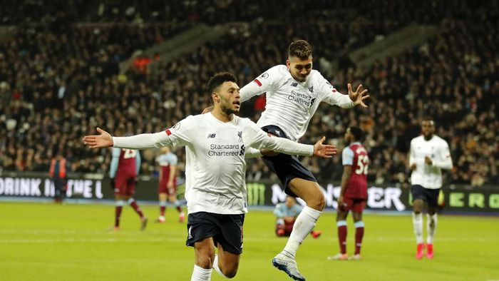 Liverpools Alex Oxlade-Chamberlain, left, celebrates with Liverpools Roberto Firmino after scoring his sides second goal during the English Premier League soccer match between West Ham Utd and Liverpool at the London Stadium in London, Wednesday, Jan. 29, 2020. (AP Photo/Frank Augstein)