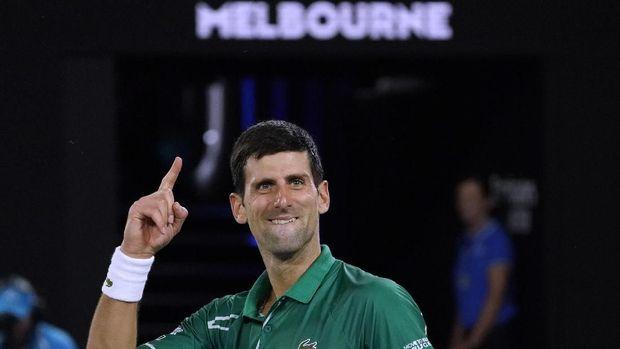 Serbia's Novak Djokovic celebrates after defeating Switzerland's Roger Federer in their semifinal match at the Australian Open tennis championship in Melbourne, Australia, Thursday, Jan. 30, 2020. (AP Photo/Lee Jin-man)
