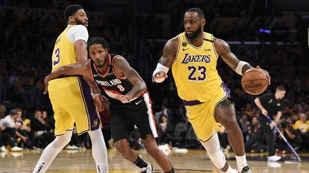 Los Angeles Lakers forward LeBron James, right, handles the ball while Anthony Davis, left, sets a screen on Portland Trail Blazers forward Trevor Ariza during the second half of an NBA basketball game in Los Angeles, Friday, Jan. 31, 2020. (AP Photo/Kelvin Kuo)