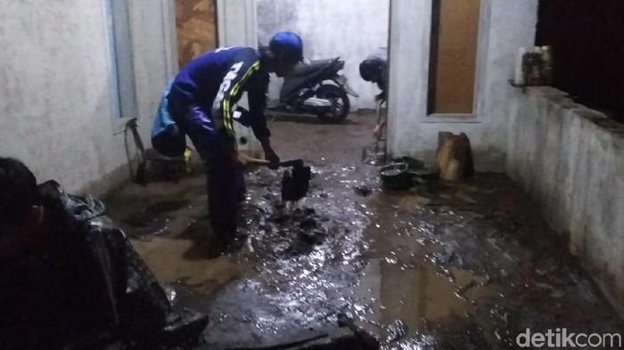 Warga membersihkan lumpur yang masuk rumah (Foto: Yakub Mulyono)