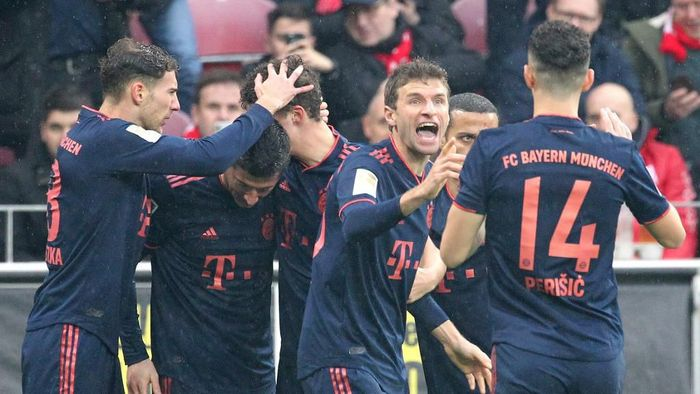 Bayern Munichs Polish forward Robert Lewandowski (2ndL) is congratulated by teammates, including German forward Thomas Mueller (2ndR) after scoring during the German first division Bundesliga football match Mainz 05 v FC Bayern Munich in Mainz on February 1, 2020. (Photo by Daniel ROLAND / AFP) / RESTRICTIONS: DFL REGULATIONS PROHIBIT ANY USE OF PHOTOGRAPHS AS IMAGE SEQUENCES AND/OR QUASI-VIDEO