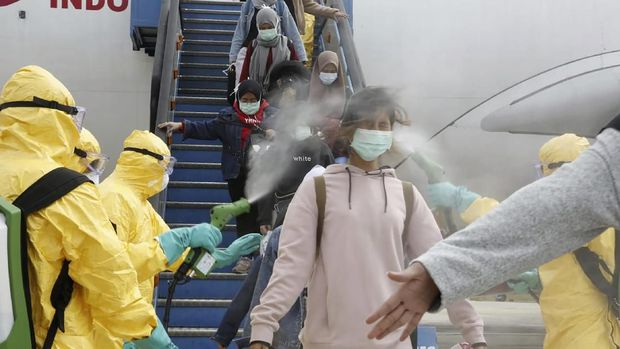 In this photo released by Indonesian Foreign Ministry, Indonesian people who arrived from Wuhan, China, are sprayed antiseptic at Hang Nadim Airport in Batam, Indonesia Sunday, Feb. 2, 2020. Indonesians evacuated from Wuhan, the Chinese city at the center of a deadly virus outbreak, were transported to a quarantine zone on a remote island at the edge of the South China Sea, shortly after landed on Batam, an island near Singapore on Sunday morning. (Indonesian Foreign Ministry via AP)