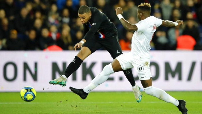 PSGs Kylian Mbappe, left, fights for the ball with Montpelliers Ambroise Oyongo during the French League One soccer match between Paris-Saint-Germain and Montpellier at the Parc des Princes stadium in Paris, Saturday Feb. 1, 2020. (AP Photo/Christophe Ena)
