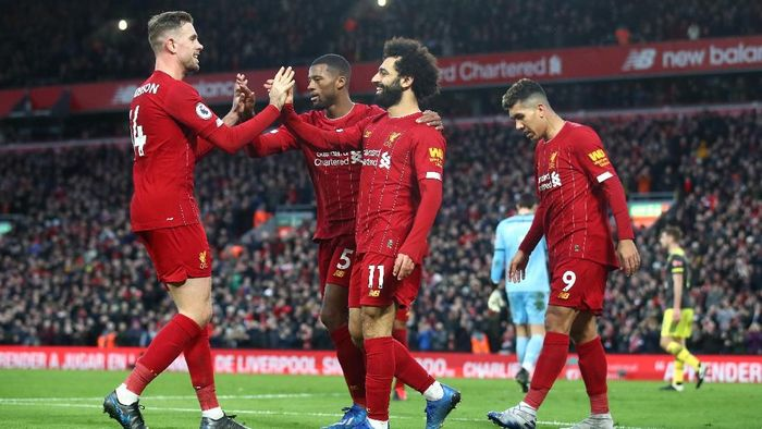 LIVERPOOL, ENGLAND - FEBRUARY 01: Mohamed Salah of Liverpool celebrates with Georginio Wijnaldum, Jordan Henderson and Roberto Firmino after scoring his teams third goal during the Premier League match between Liverpool FC and Southampton FC at Anfield on February 01, 2020 in Liverpool, United Kingdom. (Photo by Julian Finney/Getty Images)