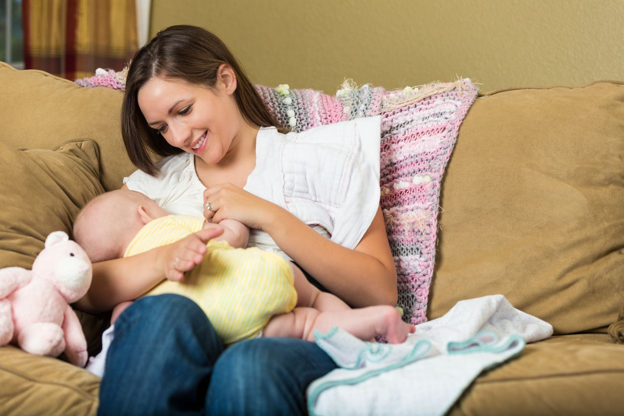 Young adult Caucasian woman is sitting on sofa at home in living room. She is breastfeeding her six month old baby daughter. Mother is smiling lovingly at baby while nursing her.