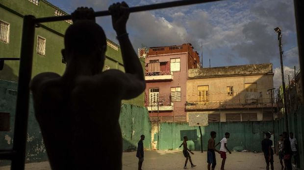 A young man exercises on a pull up bar near a pick-up soccer game, in Havana, Cuba, Wednesday, Feb. 5, 2020. (AP Photo/Ramon Espinosa)