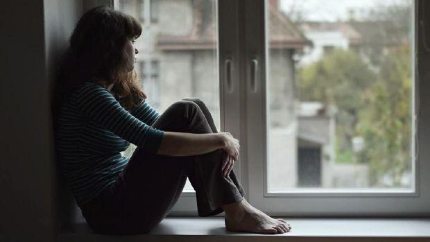 Sad young woman sitting on the window