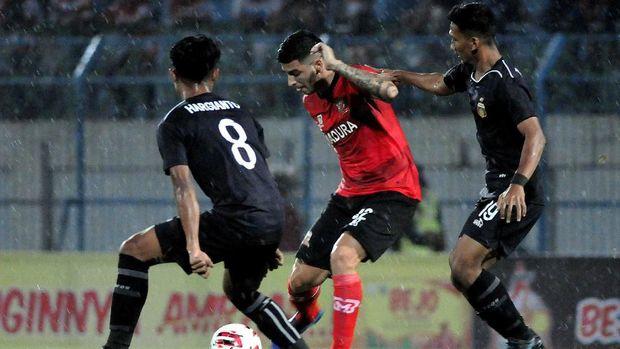 Madura United (merah) berada di posisi kedua klasemen Grup A.