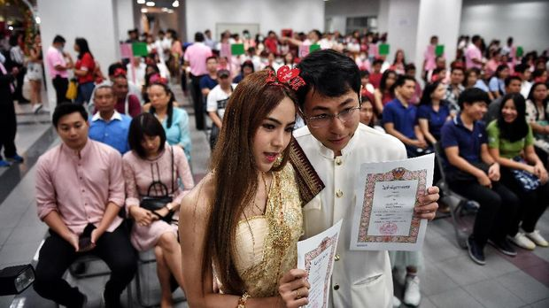 A couple shows their newly-issued marriage license on Valentine's Day in Bang Rak, the Thai capital's