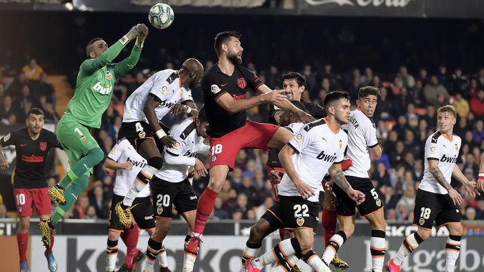 Valencias Spanish goalkeeper Jaume Domenech (L) jumps for the ball during the Spanish league football match between Valencia CF and Club Atletico de Madrid at the Mestalla stadium in Valencia on February 14, 2020. (Photo by JOSE JORDAN / AFP)