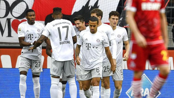 Bayerns Robert Lewandowski, center, is celebrated after scoring the opening goal during the German Bundesliga soccer match between 1. FC Cologne and Bayern Munich in Cologne, Germany, Sunday, Feb. 16, 2020. (AP Photo/Martin Meissner)