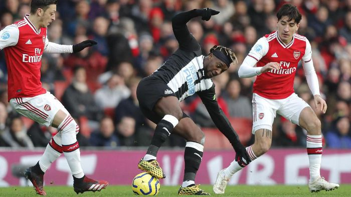 Arsenals Hector Bellerin, right, challenges for the ball with Newcastles Allan Saint-Maximin, center, during the English Premier League soccer match between Arsenal and Newcastle at the Emirates Stadium in London, Sunday, Feb. 16, 2020.(AP Photo/Frank Augstein)