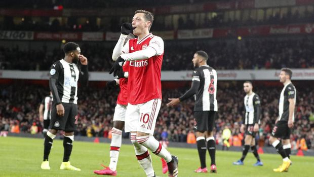 Arsenal's Mesut Ozil celebrates after scoring his side's third goal during the English Premier League soccer match between Arsenal and Newcastle at the Emirates Stadium in London, Sunday, Feb. 16, 2020.(AP Photo/Frank Augstein)